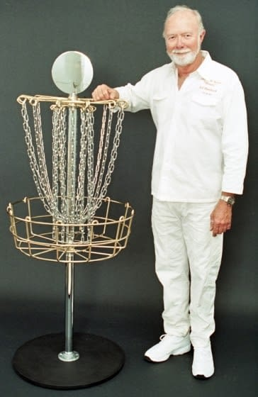 """Steady"""" Ed Headrick the father of disc golf and invented of the the first disc golf baskets poses for a disc golf hall of fame photo next to a custom gold plated DGA Mach 3 Basket."""
